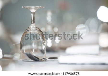 Glass of water on luxury table setting for dining, selective focus with bokeh background