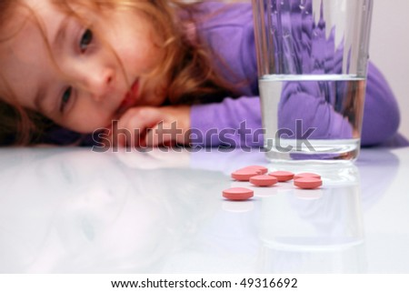 glass of water; pills and little girl