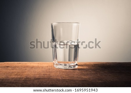 Glass of water with half full water on the table, concept of positive and negative thinking Сток-фото ©