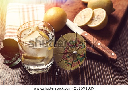 glass of water with ice and lemon on wooden table