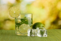 Glass of water with ice, mint and lime on table on bright background