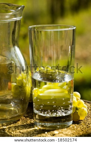 glass of water with jug and grapes