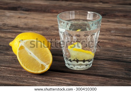 glass of water with lemon slices on a wooden background. Copy space. Free space for text