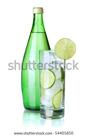 Glass of water with lime, ice, mint and bottle with mineral water. Isolated on white background