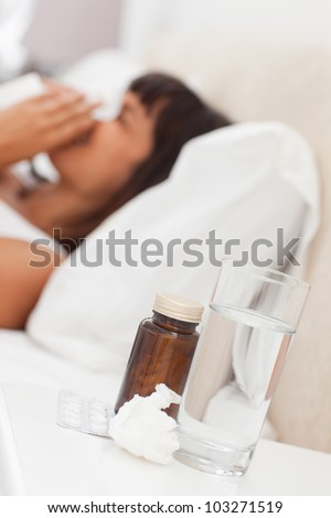 Glass of water with medicines on a beside-table with a young woman blowing in background