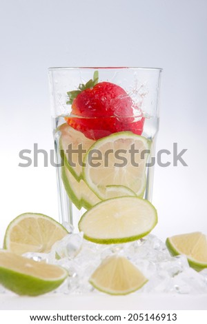 Glass of water with strawberry, lemon and lime, water splashes and droplets, surrounded by ice cubes and slices of lemon isolated on white background