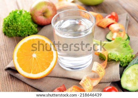 Glass of water with vegetables and measuring tape on table close-up