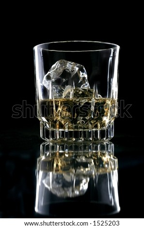 Glass of whiskey against black background.