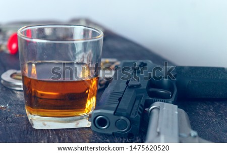 Photo of  Glass of whiskey and gun.Concept of crime and alcohol relation.