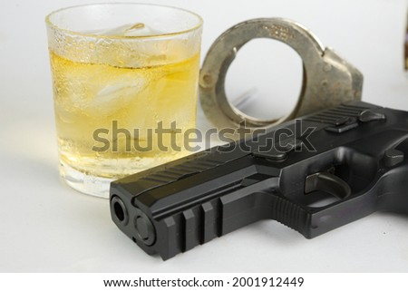 Glass of whiskey and gun.Concept of crime and alcohol relation. Foto stock ©