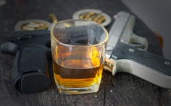 Glass of whiskey and gun.The relationship of alcohol and crime.