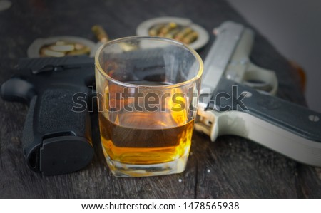 Photo of  Glass of whiskey and gun.The relationship of alcohol and crime.