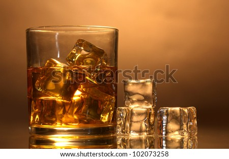 glass of whiskey and ice on brown background