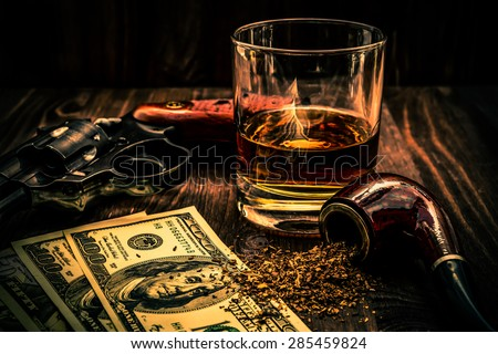 Glass of whiskey and revolver with a… Stock Photo 285765845 - Avopix com