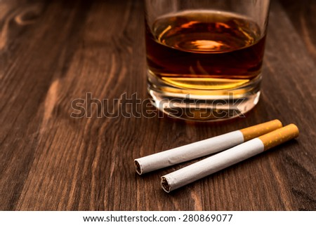 Glass of whiskey and two cigarettes on a wooden table. Focus on the cigarettes