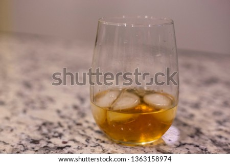 Glass of whiskey on granite counter ice on the rocks scotch bourbon brown liquor alcohol cocktail mix sip drink drunk