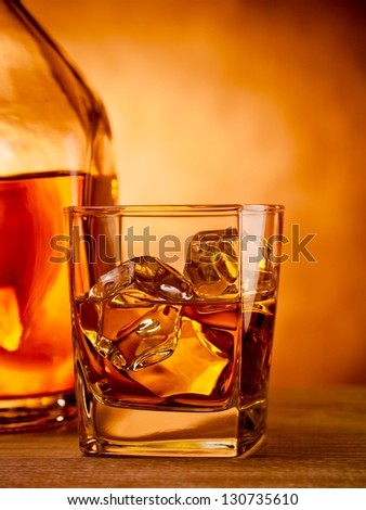 Glass of whiskey on the rocks next to a bottle