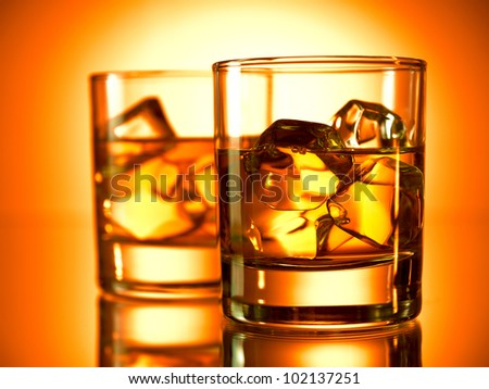 Glass of whiskey on the rocks with a bottle in the background