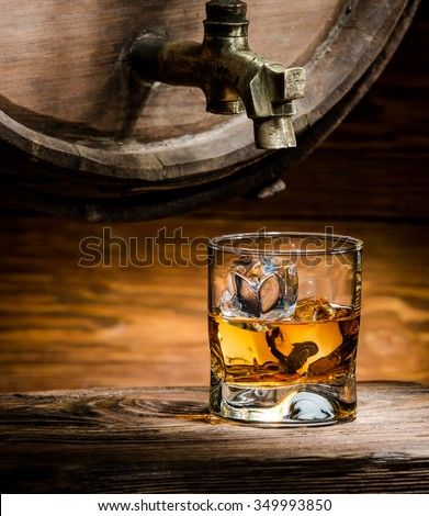 glass of whiskey or brandy ice poured from an old oak barrel