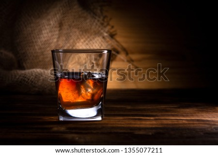 glass of whiskey or cognac on a wooden background #1355077211