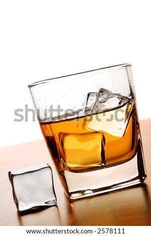 Glass of Whiskey with ice cube - stock photo