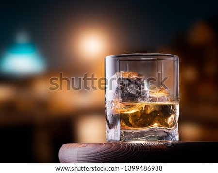 Glass of whiskey with ice cubes on the wooden table with city view background #1399486988