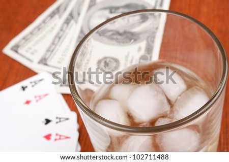 Glass of whiskey with ice cubes, poker of aces and hundred-dollar bills on the wooden table