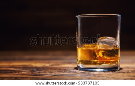 Glass of whiskey with ice cubes served on wooden planks. Vintage countertop with highlight and a glass of hard liquor #533737105