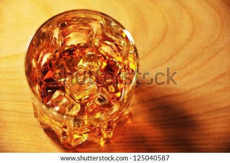 Glass of whiskey with ice on a wooden table top view