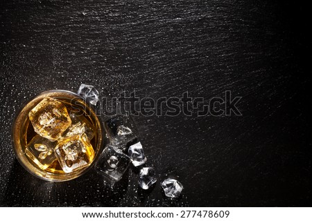 Glass of whiskey with ice on black stone table. Top view with copy space #277478609