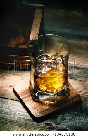 Glass of whiskey with ice on wooden lining and planking texture