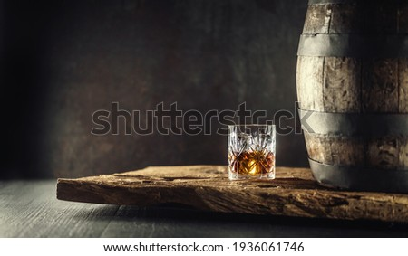 Glass of whisky cognac or bourbon in ornamental glass next to a vinatge wooden barrel on a rustic wood and dark background.