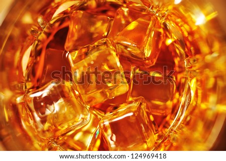 Glass of whisky with ice close-up view from above