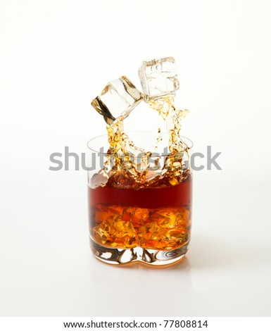 Glass of whisky with ice. The pair of cubes of ice jumps out of a glass. A white background.