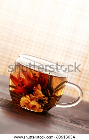 glass of white tea with beauty tea flower inside - tea time