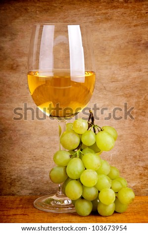 glass of white wine and grapes on a vintage wooden background