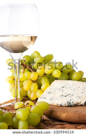 glass of white wine, blue cheese and a bunch of white grapes on white background