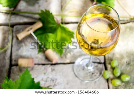 Glass of white wine on top of the background of stone, corkscrew and cork, vine leaves and grapes.