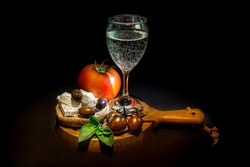 Glass of white wine, white cheese feta with oregano, olives, cherry, tomato and dry rye bread on a wooden chopping board. Isolated on black background