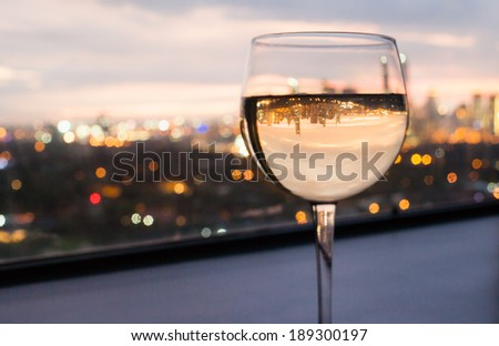 Glass of white wine with city view.