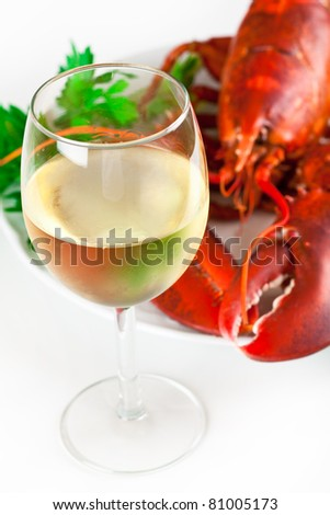 Glass of white wine with cooked lobster on the plate, top view