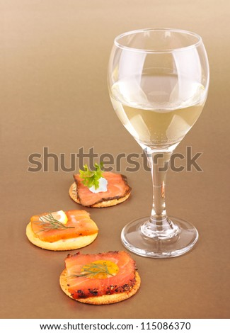 Glass of wine and appetizers on golden background