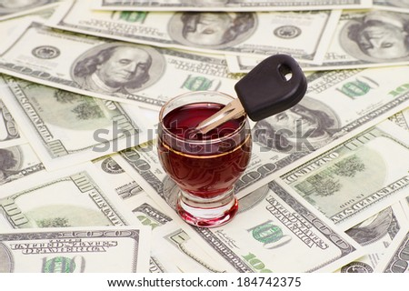 glass of wine and car key on a background of 100 dollar bills. concept to quit drinking