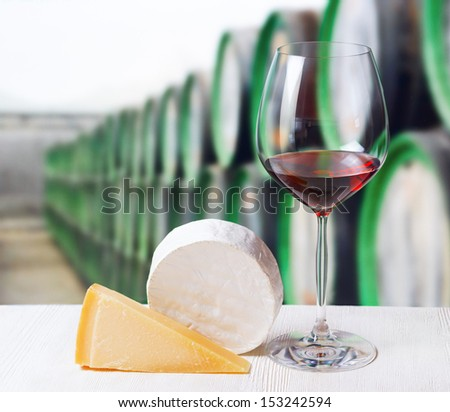 Glass of wine and cheese in winery.