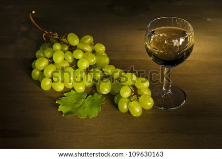 glass of wine and cluster of grapes, wooden table - stock photo