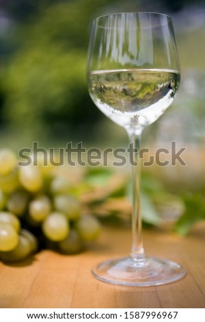 Glass of wine and grapes on table