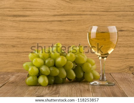 glass of wine and vine on a wooden table #118253857