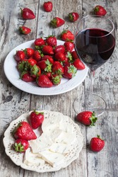 glass of wine, cheese and fresh strawberries on wooden table