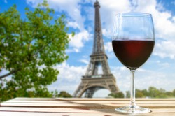 Glass of wine on a table with Eiffel tower. Sunny view of glass of red wine overlooking the Eiffel Tower in Paris, France