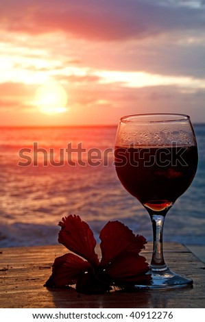 Glass of wine on the see shore with a flower